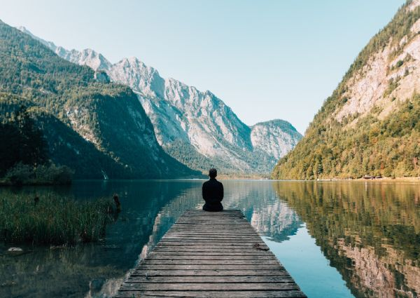 person experiencing peace of mind on a dock overlooking water and mountains