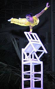 woman balances on chairs